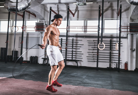 Muscular man skipping exercise with jumping rope at gym