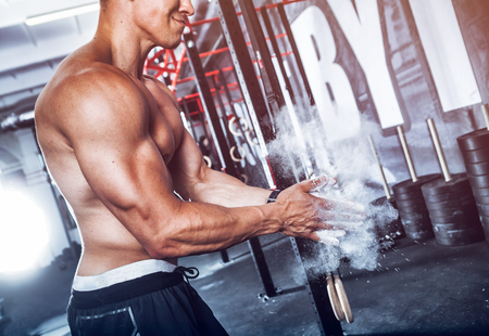 magnesia: Muscular bodybuilder preparing for training with magnesia at gym Stock Photo