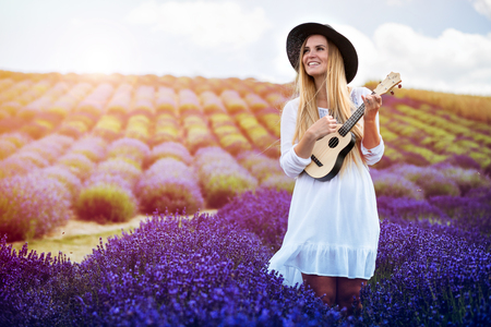 Beautiful boho girl playing ukulele in lavender field at summer day, hippie fashion style