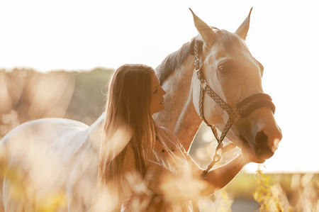 Woman with her horse at sunset, autumn outdoors scene Stock Photo