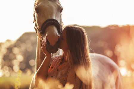 Donna bacia il suo cavallo al tramonto, autunno scena all'aperto