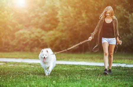 Pretty girl walking dog at the park, samoyed