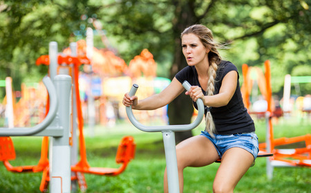 Woman exercising at outdoors gym playground equipment Stock Photo
