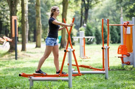 여자는 야외 체육관 놀이터 장비에서 운동