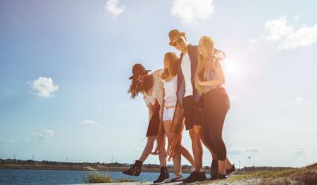 Groupe d'amis heureux marchant sur la plage, style de mode Banque d'images - 87555217