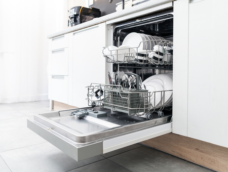 Open dishwasher with clean dishes in the white kitchen Foto de archivo