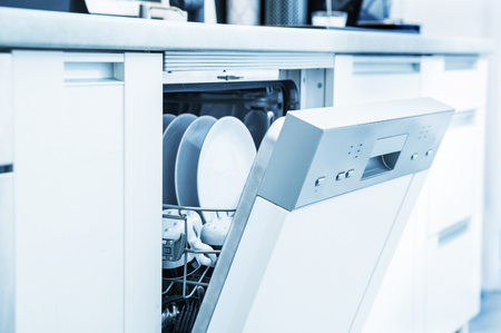 Open dishwasher with clean dishes in the white kitchen Archivio Fotografico
