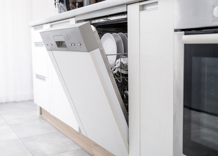 Open dishwasher with clean dishes in the white kitchen Banque d'images