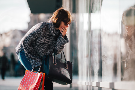Shocked woman on street looking at shopping window, shopaholic concept Stock Photo