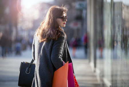 Woman during walk on the street with shopping bags