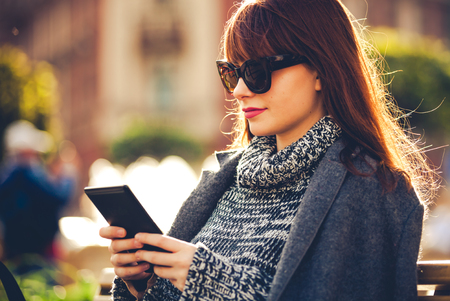 Pretty woman using tablet or ebook reader sitting in town street pretty woman using tablet or ebook reader sitting in town street urban scene photo fandeluxe Ebook collections