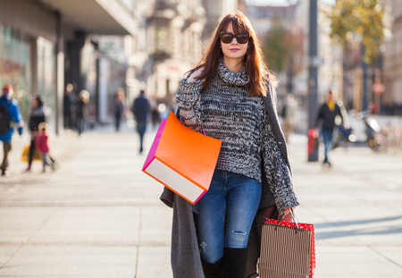 Urban scene, woman with shopping bags walking down the street