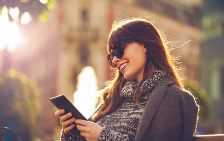 Pretty woman using tablet or ebook reader sitting in town street smiling woman using tablet or ebook reader sitting on bench at the city urban scene fandeluxe Ebook collections