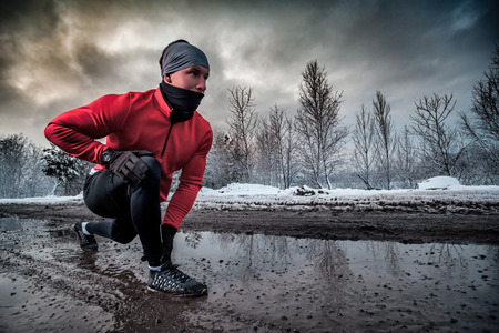 Runner man running in dirty puddle at winter time, outdoor exercise