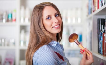 Beautiful customer woman at beauty store choosing cosmetics with make up brush
