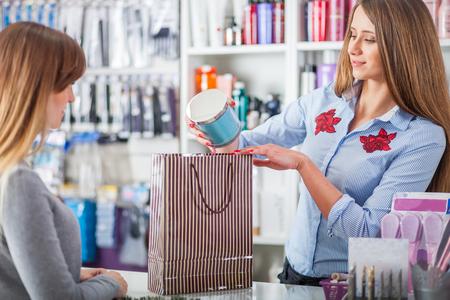 Beautiful saleswoman at beauty store putting cosmetics into shopping bag for customer 免版税图像