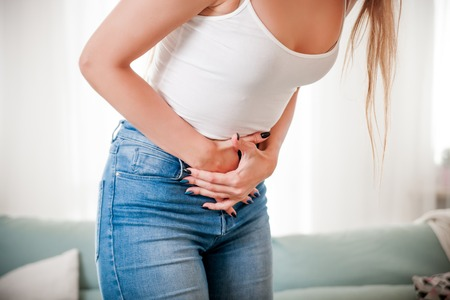 Young female at home suffering from abdominal pain, close up Stock Photo