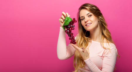 Woman with grape over pink background Stock Photo