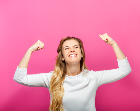 Successful woman raising hand in success gesture over pink background