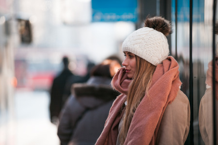 Beautiful woman in wool hat waiting at bus stop during cold winter day
