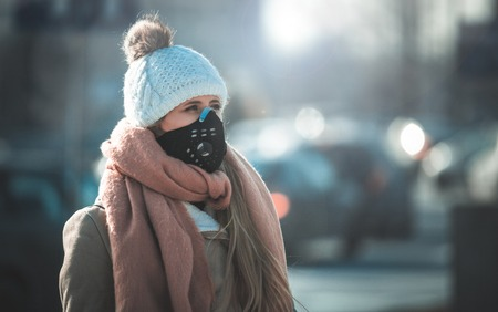 Young woman wearing protective mask in the city street, smog and air pollution during winter Фото со стока