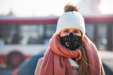 Young woman wearing protective mask in the city street, smog and air pollution during winter Standard-Bild