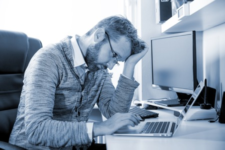 Overworked tired man at workplace in office being unhappy