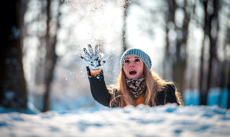 Young woman throwing snowball at sunny day in the winter park