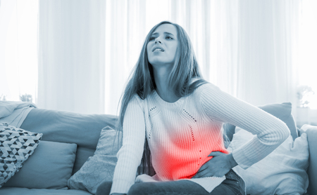 Young woman suffering from abdominal pain while sitting on sofa at home