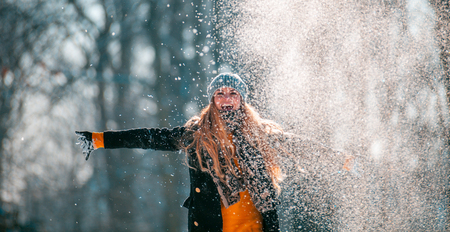 Smiling young woman throwing snow in the air at sunny winter day Stock fotó