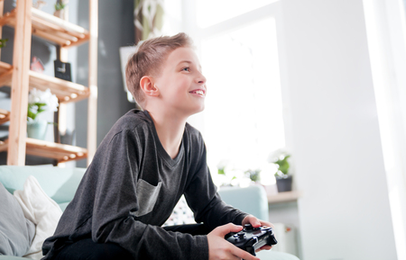 Excited young boy playing game on the console sitting on coach at home
