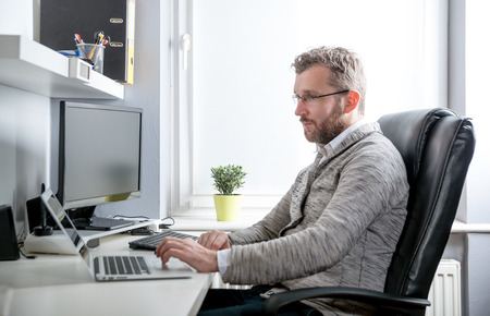 Middle age man working in home office with computer laptop