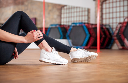Injured fit woman feeling pain in her ankle at fitness gym