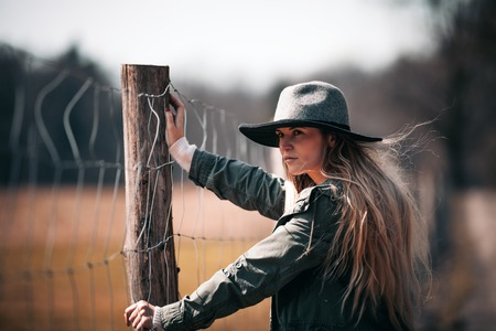 Portrait of stylish woman with long hair in hat on rural country farm