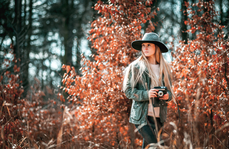 Beautiful girl with vintage camera in golden autumn forest Stock Photo
