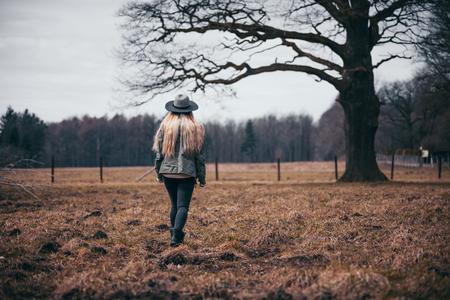 Rural scene with woman in hat walking on field, melancholic autumn mood