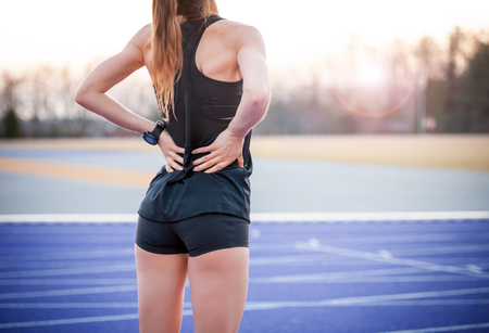 Athlete woman has back pain, muscle injury during running training Foto de archivo