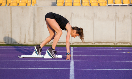 Athletic woman on running track starting from start line