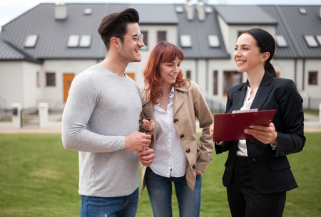 Real estate agent talking with young couple about buying new house in residential area