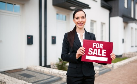 Real estate agent with sign For Sale on placard in front of house, copy space