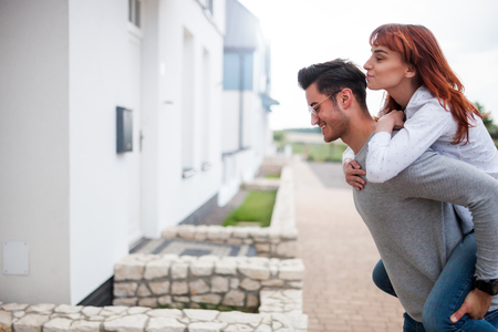 Man carrying wife on his back in front of their new home, happy couple after buying real estate Stock fotó