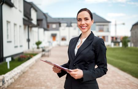Agente de bienes raíces en frente de la casa en venta listo para presentar oferta, espacio de copia Foto de archivo