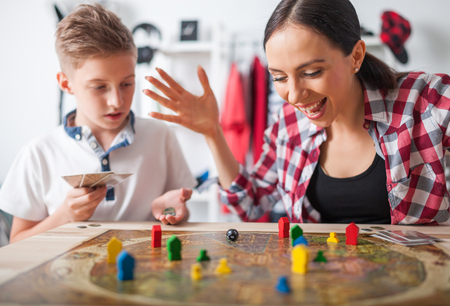 Mother and son playing modern board game in teenage room at home Foto de archivo