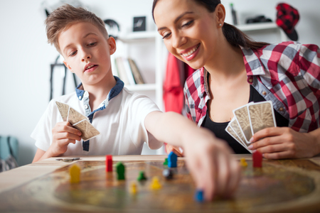 Mother and son playing modern board game in teenage room at home Archivio Fotografico