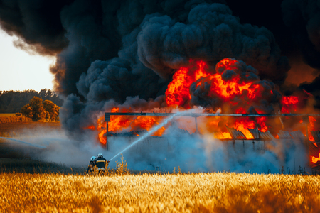 Firefighters with hose in front of huge fire among fields