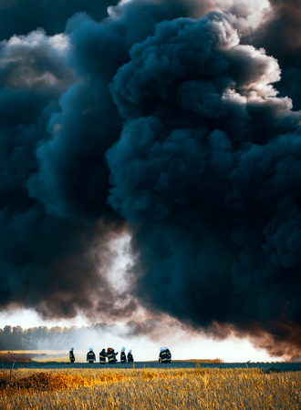 Firefighters standing under huge black cloud of smoke from the fire