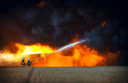 Firefighters spraying water in front of huge fire and black smoke Stock Photo