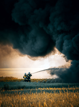 Dramatic scene. Firefighters against huge fire standing under black cloud of smoke Stock Photo