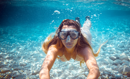 Girl snorkeling underwater in the tropical sea