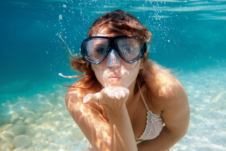 Woman underwater snorkeling in the clear tropical water and blowing a kiss